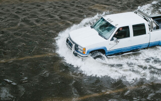 A truck drives through water on a flooded street in downtown Jacksonville, Florida, in 2017 during Hurricane Irma's Aftermath. Photo by Wade Austin Ellis on Unsplash.